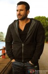 Saif Ali Khan glances away in a hooded grey jacket
